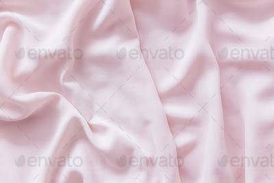 Pink wrinkled silk fabric. The pink fabric is laid out waves. Pink fabric background or texture.