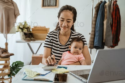 young mother with little daughter are working with calculator and laptop