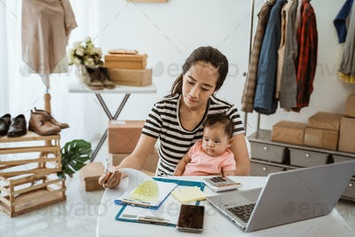 young asian business mother with little daughter are writing when work