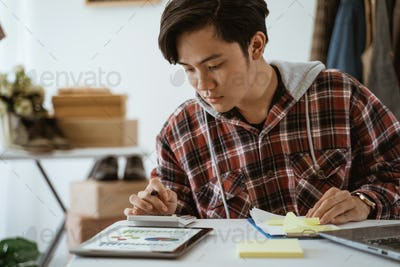asian young business store owner taking note from customer