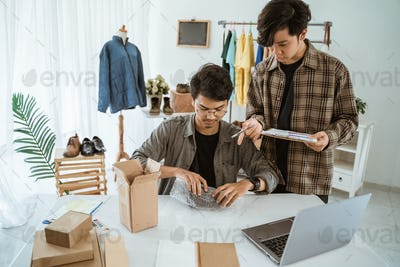 young asian people businessman chatting about packaging of camera lens