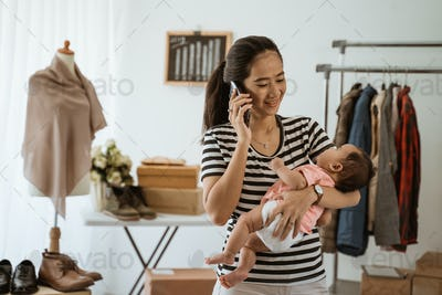 young asian business mother with carrying little daughter work using phone