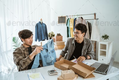 Two young asian businessman chatting about their clothing product