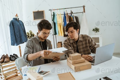 Two young asian businessman chatting about their product