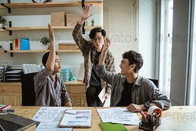 three young Asian workers work together in agreement at planning