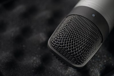 Gray studio condenser microphone on black soft foam