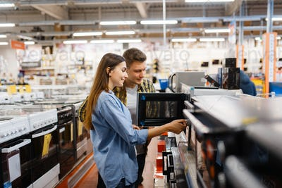 Couple choosing microwave in electronics store