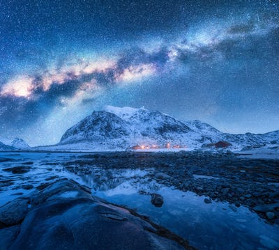 Milky Way above frozen sea coast and snow covered mountains