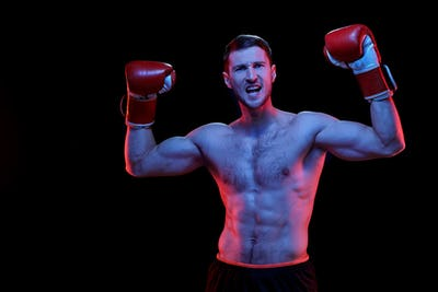 Ecstatic young muscular shirtless sportsman in boxing gloves raising arms