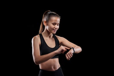 Pretty young smiling sportswoman in activewear looking at her smartwatch