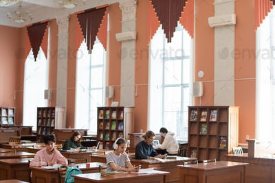 Two rows of desks in college library and students working individually