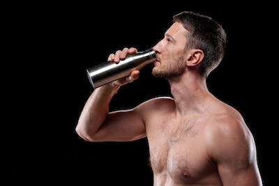 Young athlete standing in front of camera and drinking water from metal bottle