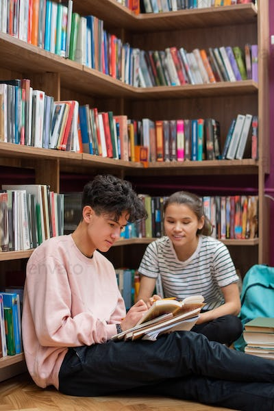 Two clever teenage students discussing passage from story in library