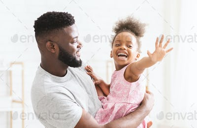 Close up portrait of man holding his happy little daughter