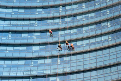 Window cleaners suspended on side of a skyscraper