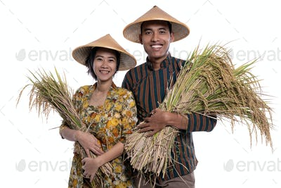 traditional male and female asian farmer with rice paddy grain in hand smiling to camera