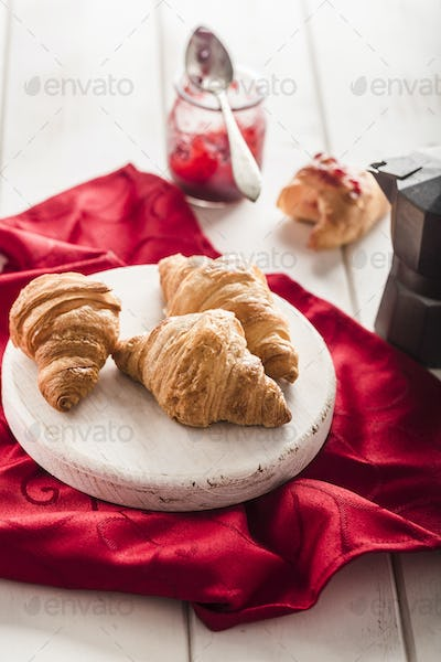 Freshly baked French croissants with a jar of jam on a light wooden background with a red napkin.