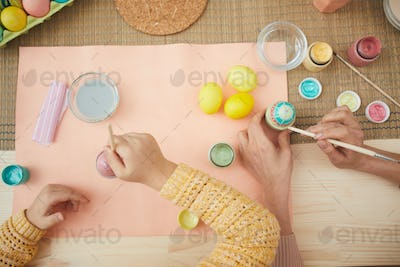 Above View of Little Girl Painting Easter Eggs