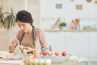 Young Woman Hand-Painting Easter Eggs