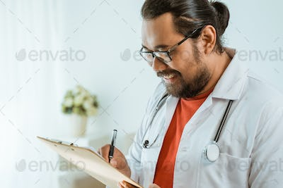 doctor with clipboard writing and reading prescription
