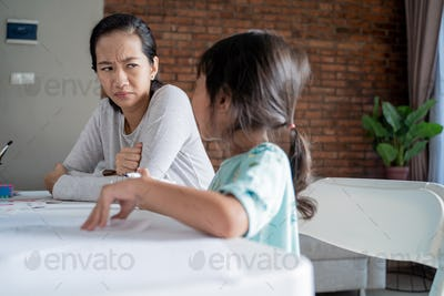 unhappy mother while teaching her daughter at home