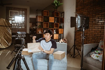 asian young man vlogger recording new vlog about unboxing review