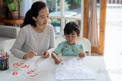 mother teaching basic math to her little daughter