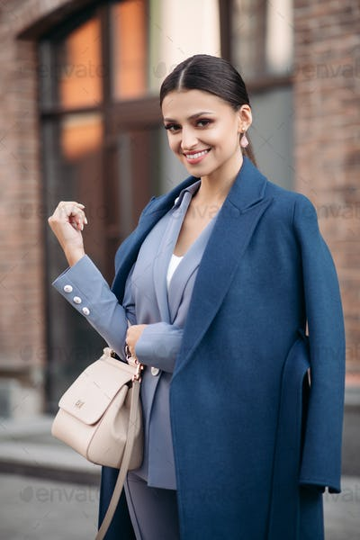Attractive cheerful brunette in suit and coat
