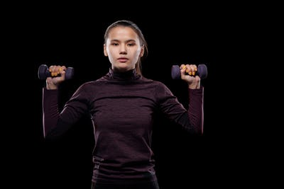 Young sportswoman in activewear looking at you during exercise with dumbbells