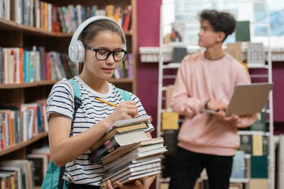 Pretty girl in headphones and eyeglasses making list of literature in library