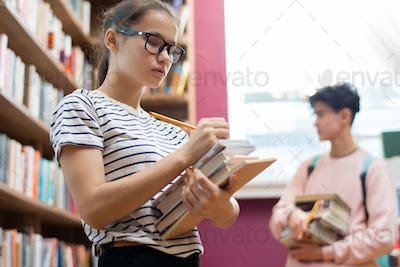 Clever teenager in eyeglasses making notes in notepad on top of stack of books
