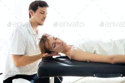 Young physiotherapist doing a neck treatment to the patient in a physiotherapy room.