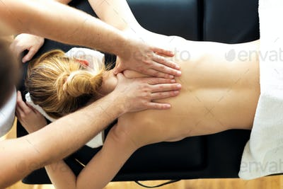 Young physiotherapist doing a back treatment to the patient in a physiotherapy room.