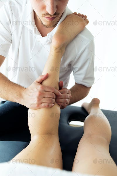 Young physiotherapist doing a legs treatment to the patient in a physiotherapy room.