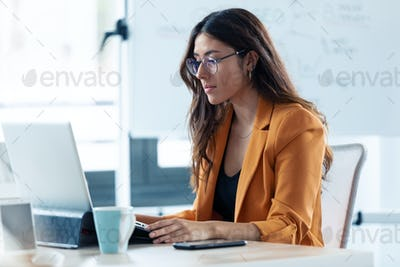 Business young woman working with laptop in the office.