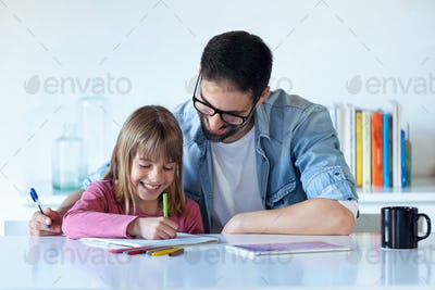 Handsome young father with his daughter drawing on notebook at home.