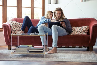 Lovely young couple drawing with they digital tablet while sitting on sofa at home.