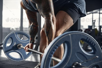 The male athlete training hard in the gym. Fitness and healthy life concept