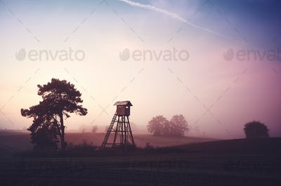 Rural landscape with silhouette of hunting tower on a field at sunrise.