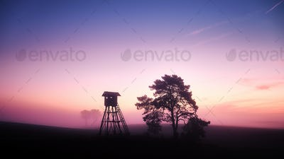 Rural landscape with silhouette of hunting tower at sunrise