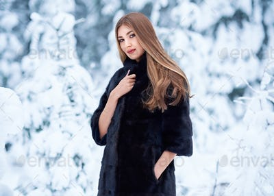 Fashion young woman in the winter forest