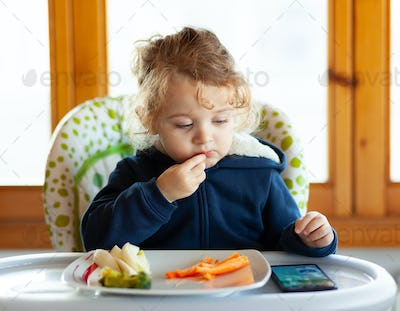 Toddler eats while watching movies on the mobile phone.