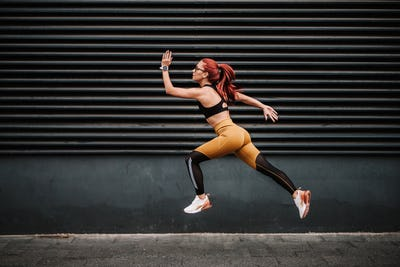 Sports and fitness concept - Young woman with fit body jumping and running, exercising
