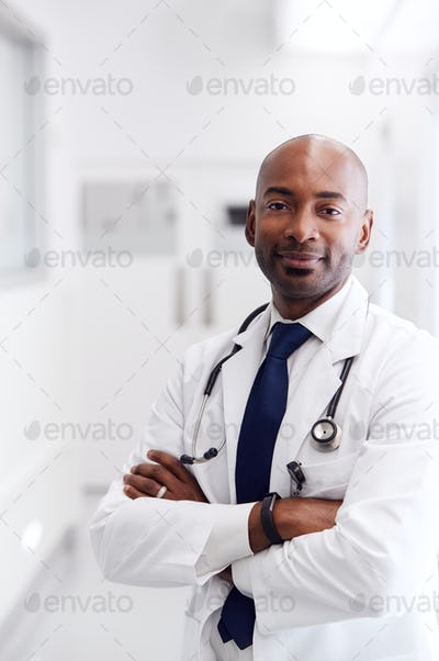 Portrait Of Mature Male Doctor Wearing White Coat Standing In Hospital Corridor