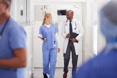 Doctor In White Coat And Nurse In Scrubs Having Discussion In Hospital Corridor