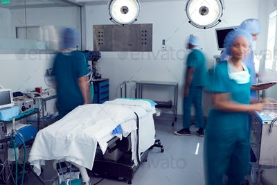 Motion Blur Shot Of Surgical Team Wearing Scrubs In Busy Hospital Operating Theater