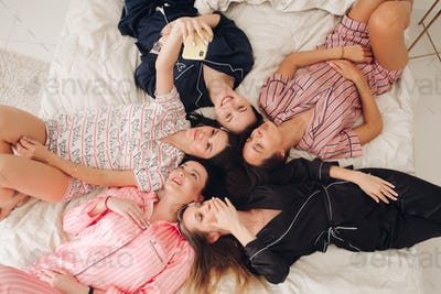 Pretty girls in pyjamas taking selfie on bed