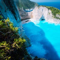 Wide view of Navagio beach with green vegetation in foreground. Famous landscape of Zakinthos island