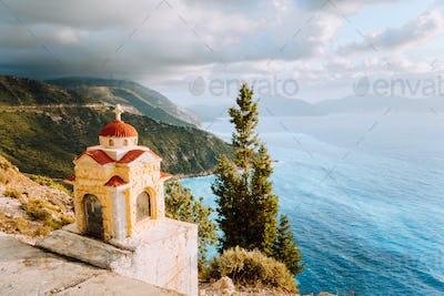 Colorful Proskinitari shrine lantern on pedestal on the cliff edge. Amazing coastline view with