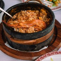 National cuisine of Cape Verde: Cachupa with prawn in traditional stone bowl with vegetable salad on